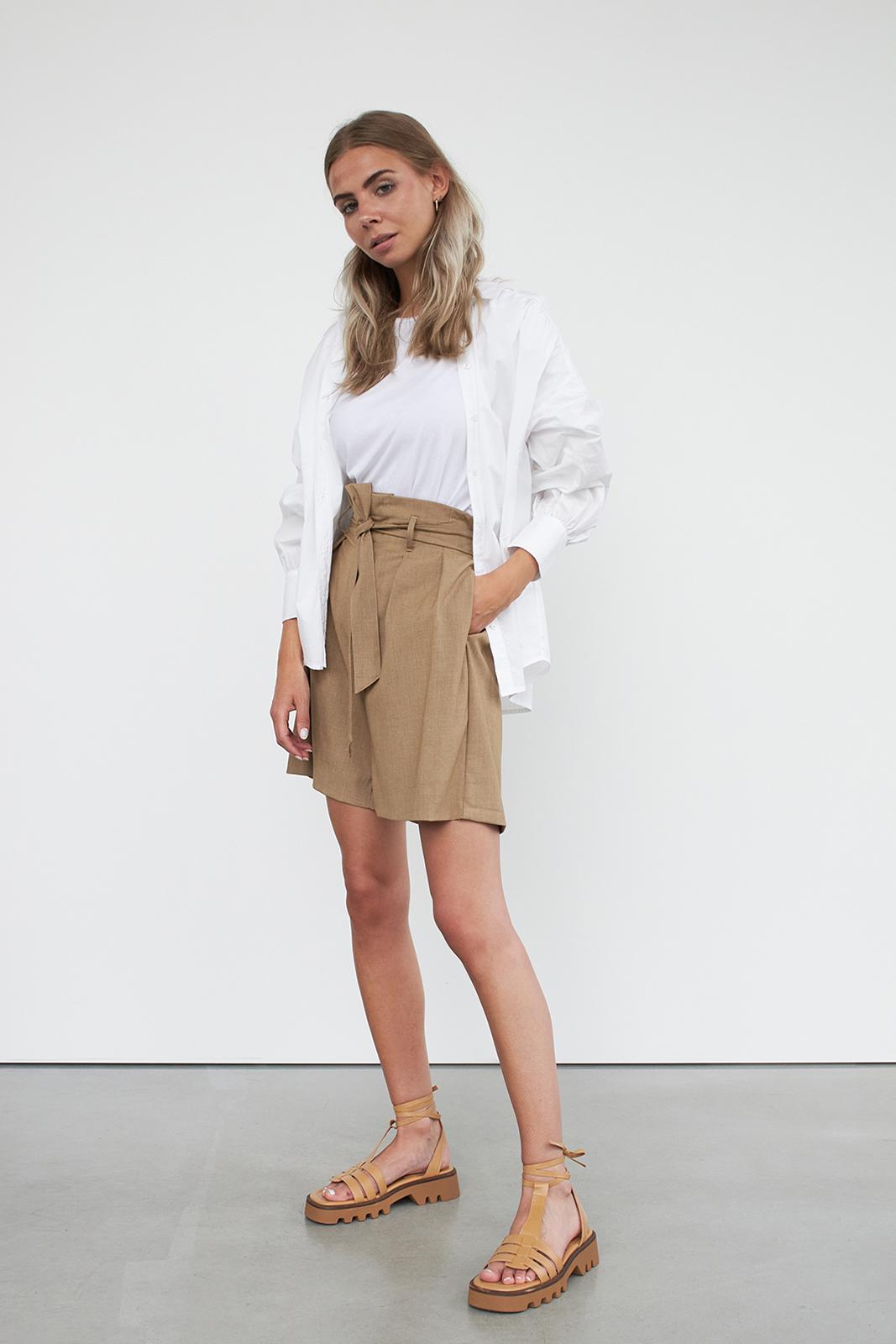 woman wearing shorts, shirt and t-shirt