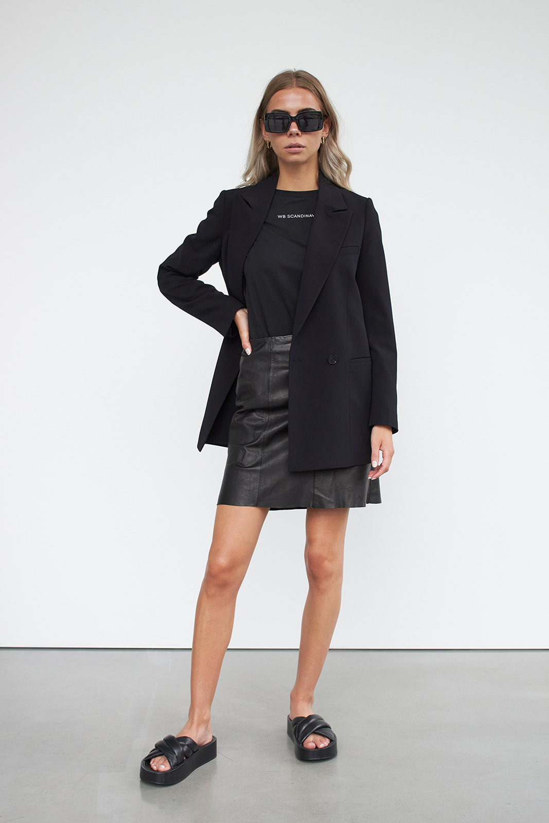 woman wearing leather skirt, t-shirt and blazer