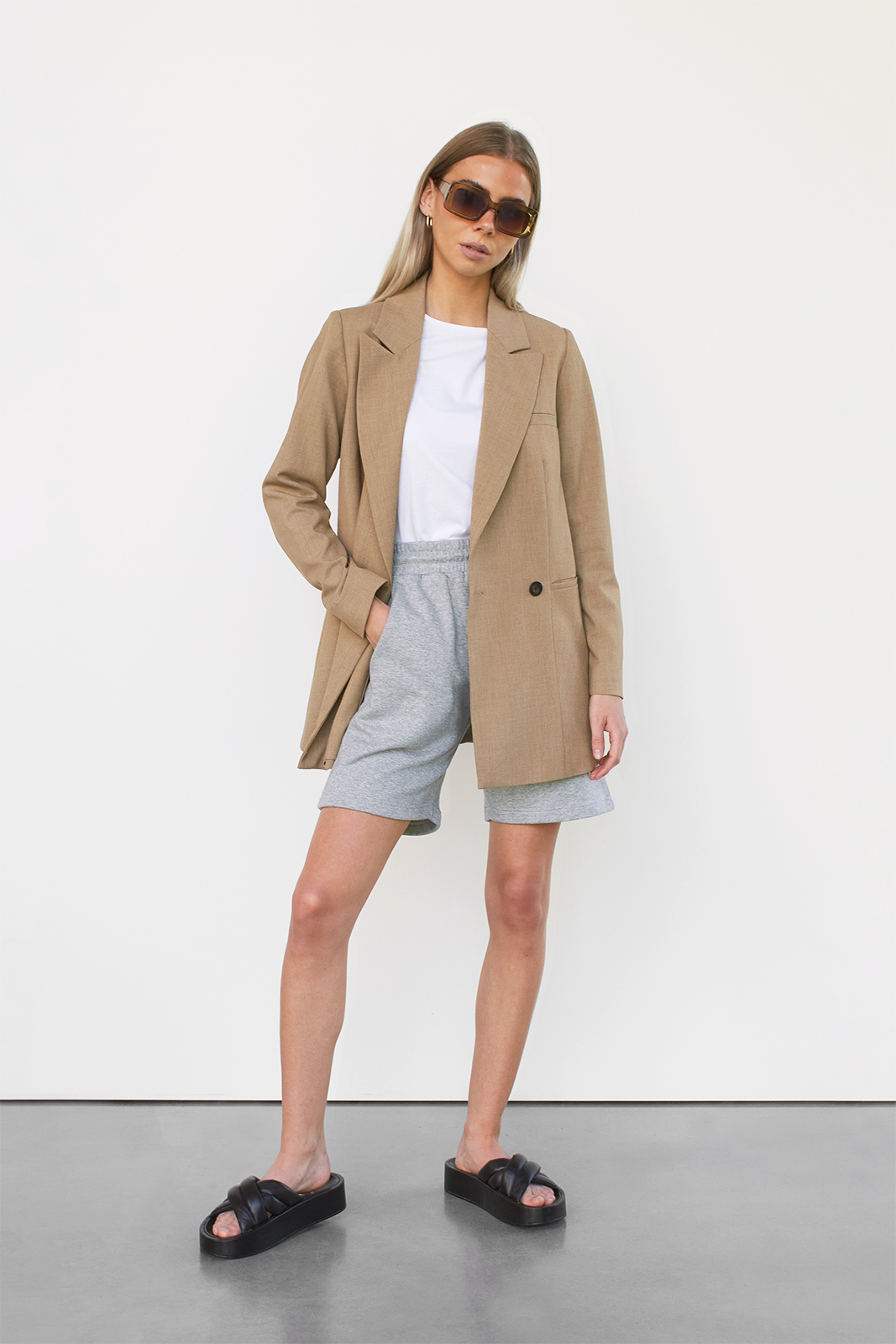 woman in blazer, shorts and white tee