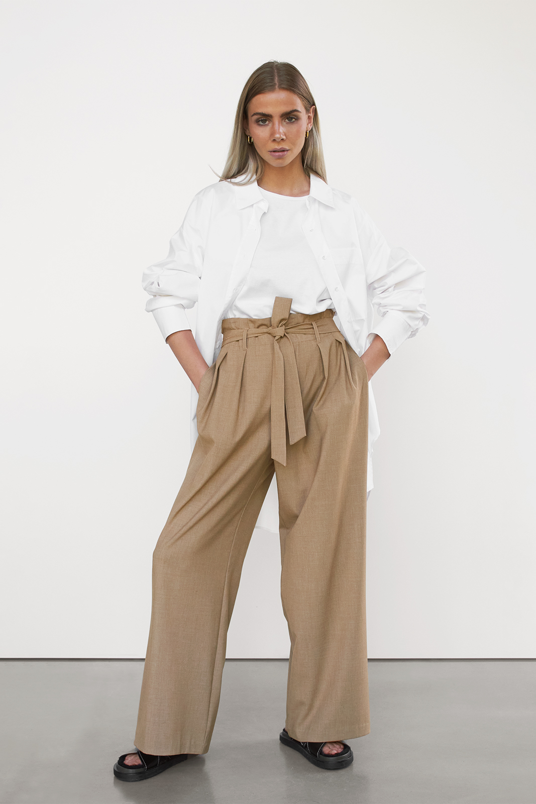 woman in loose pants, white tee and white shirt